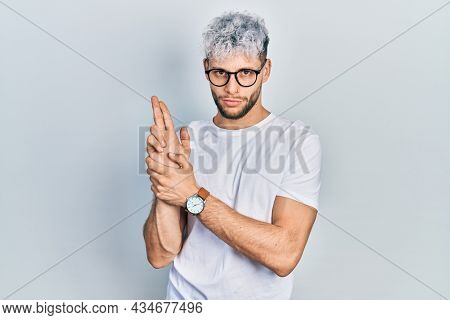 Young hispanic man with modern dyed hair wearing white t shirt and glasses holding symbolic gun with hand gesture, playing killing shooting weapons, angry face