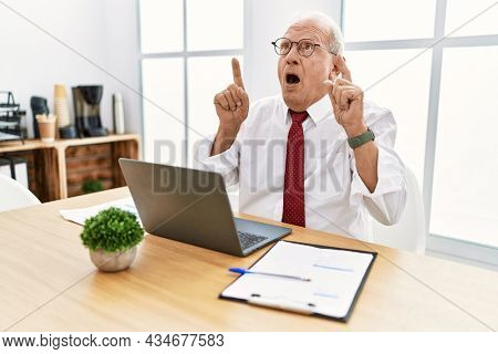 Senior man working at the office using computer laptop amazed and surprised looking up and pointing with fingers and raised arms.