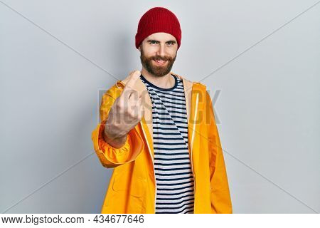 Caucasian man with beard wearing yellow raincoat beckoning come here gesture with hand inviting welcoming happy and smiling