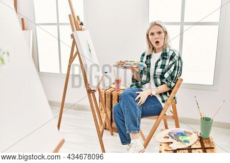 Young artist woman painting on canvas at art studio in shock face, looking skeptical and sarcastic, surprised with open mouth