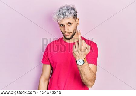 Young hispanic man with modern dyed hair wearing casual pink t shirt showing middle finger, impolite and rude fuck off expression