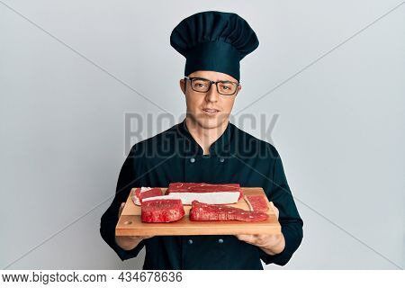 Handsome young man wearing chef uniform holding board with raw meat in shock face, looking skeptical and sarcastic, surprised with open mouth