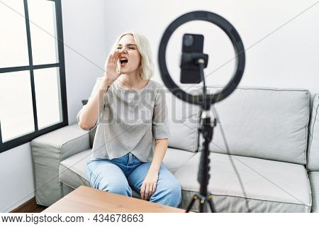 Young caucasian woman recording vlog tutorial with smartphone at home shouting and screaming loud to side with hand on mouth. communication concept.