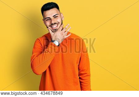 Young hispanic man with beard wearing casual orange sweater looking confident at the camera smiling with crossed arms and hand raised on chin. thinking positive.