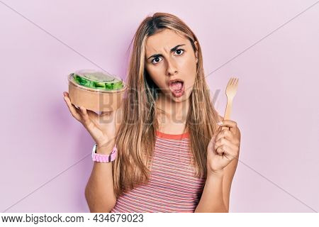 Beautiful hispanic woman eating salad in shock face, looking skeptical and sarcastic, surprised with open mouth