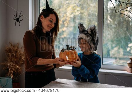 Mom And Son In Halloween Costumes Play Together With Jack-o-lantern Spooky Pumpkins Lamp At Home. Ha
