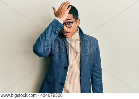 Young handsome hispanic man wearing elegant clothes and glasses surprised with hand on head for mistake, remember error. forgot, bad memory concept.