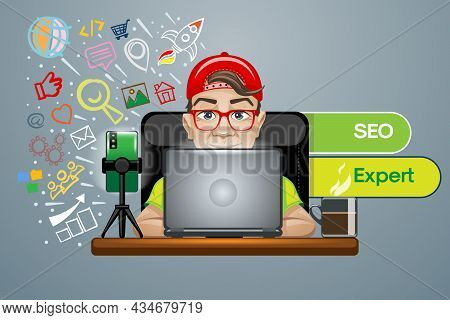 Trendy Guy In A Red Cap And Glasses At The Laptop Works As Seo Expert.