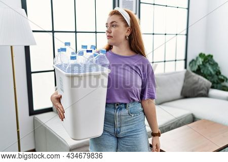 Young redhead woman holding recycling wastebasket with plastic bottles looking to side, relax profile pose with natural face and confident smile.