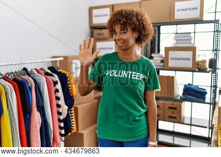Young african american woman wearing volunteer t shirt at donations stand waiving saying hello happy and smiling, friendly welcome gesture