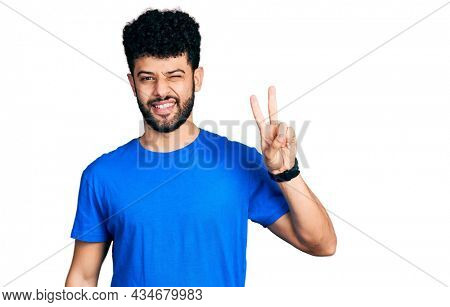 Young arab man with beard wearing casual blue t shirt smiling with happy face winking at the camera doing victory sign with fingers. number two.