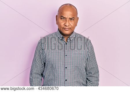 Middle age latin man wearing casual clothes skeptic and nervous, frowning upset because of problem. negative person.