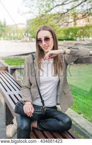 Beautiful Fashion Stylish Woman With Eyeglasses Sitting On The Bench In The City
