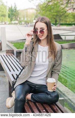 Beautiful Young Fashion Stylish Woman With Cup Of Coffee Sitting On The Bench