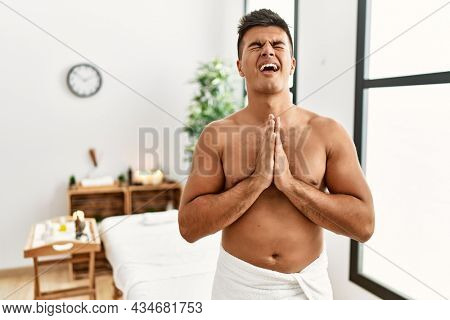 Young hispanic man standing shirtless at spa center begging and praying with hands together with hope expression on face very emotional and worried. begging.