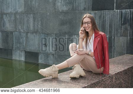 Beautiful Young Fashion Stylish Woman Talking On The Phone And Laughing Sit On Parapet