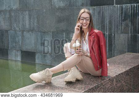 Beautiful Young Fashion Stylish Woman Talking On The Phone Sitting On Parapet