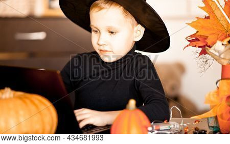 Funny Kid Boy In Witch Costume For Halloween Using A Digital Tablet Laptop Notebook. Online Call Fri