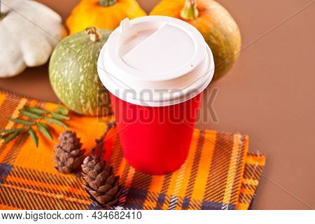 Composition With Red Paper Cup With Tea, Autumn Leaves And Small Pumpkins On The Brawn Background. A