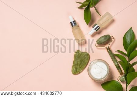 Jade Roller And Gua Sha Massager With Cream And Serum Bottles At Pastel Background. Anti-aging Thera