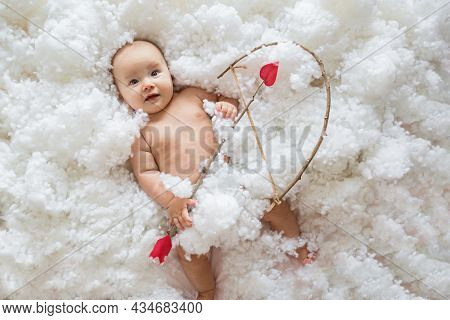 Cute Smiling Caucasian Baby Cupid On White Clouds Background With Bow And Heart Arrow. Happy Valenti