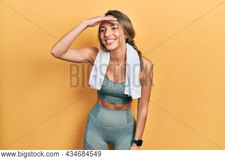 Beautiful hispanic woman wearing sportswear and towel very happy and smiling looking far away with hand over head. searching concept.
