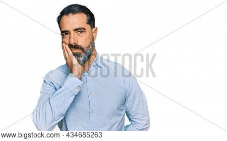 Middle aged man with beard wearing business shirt thinking looking tired and bored with depression problems with crossed arms.