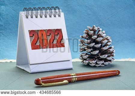 2022 number in letterpress wood type on a spiral desktop calendar with a decorative frosty pine cone against handmade paper, New Year, time management and business concept