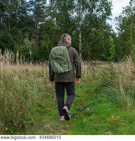 A Man With A Green Backpack On His Back And A Thermos Walks Through The Woods For A Walk. Tourist On