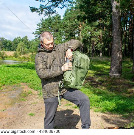 A Man With A Green Backpack And A Metal Thermos With Tea Or Coffee Walks Through The Forest For A Wa