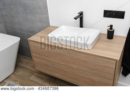 A Modern Sink In The Bathroom With A Matte Black Tap, The Floor Is Covered With Ceramic Tiles Imitat