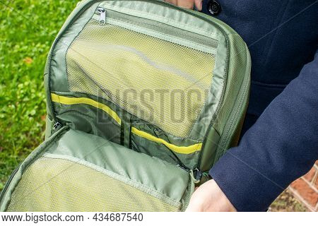 The Man's Hand Opens The Protective Pocket Of The Backpack. Organizer Panel For Various Accessories.