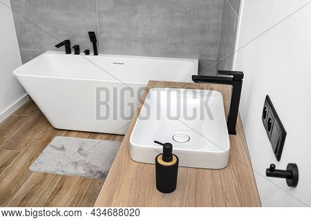 A Modern Washbasin In The Bathroom In A Wall Mounted Cupboard With A Matte Black Faucet, A Wall Line