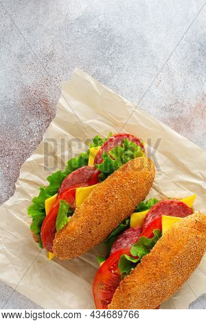 Healthy Sandwiches With Bran Bread, Green Lettuce, Cheese, Red Tomato And Sliced Salami On Parchment