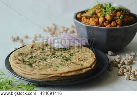 Perfectly Round Indian Flatbread Made Of Wheat Flour. Topped With Sesame Seeds And Coriander Leaves.