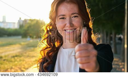 Happy Young Woman With Long Loose Curly Hair And Freckles Shows Thumb-up At Bright Backlit On City P