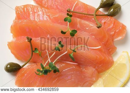 Delicious Salmon Carpaccio With Capers, Microgreens And Lemon On White Background, Top View