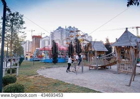 Maltepe, Istanbul, Turkey - 07.22.2021: A Family Having Fun With Amusement Park Equipment In The Eve