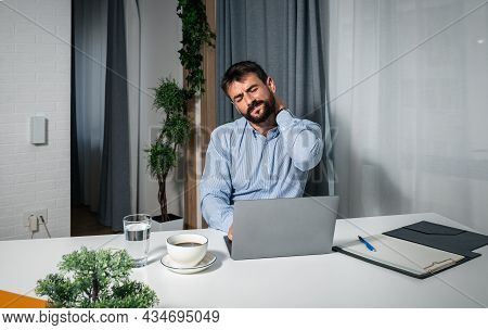 Young Successful Freelancer Businessman Manager Is Sitting At Work In The Office With A Laptop And H