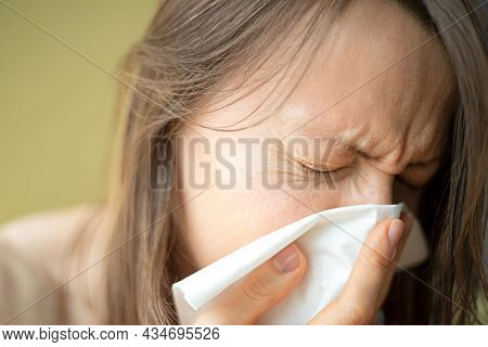 Having A Cold Or Corona Virus Flu Symptoms. Young Woman With A An Allergy Sneezing Into Her Handkerc