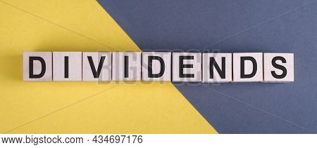 Word Dividends On Wooden Cubes On Yellow - Gray Background.