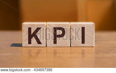 Kpi - Key Performance Indicator, Text On Wooden Cubes On Orange Wall Background.