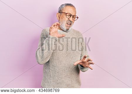 Handsome senior man with beard wearing casual sweater and glasses disgusted expression, displeased and fearful doing disgust face because aversion reaction.