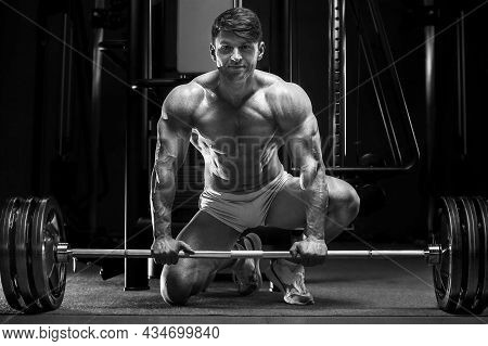 Handsome Strong Athletic Man Next To A Barbell