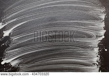 Soap Foam On A Black Table. Foam Traces On Black Background.