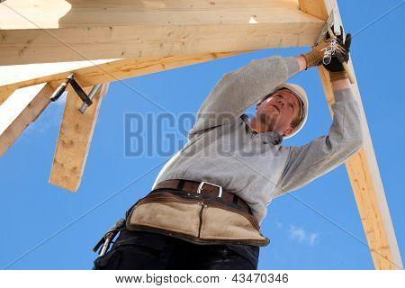 Zimmermann bei der Arbeit mit hölzernen Dachkonstruktion