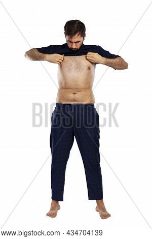 The Man Puts On A T-shirt. Young Brunette Guy. Full Height. Isolated On White Background. Vertical.