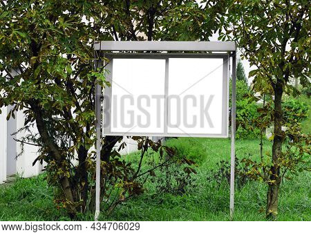 Mock-up Of A Street Advertising Sign With An Empty Space For Text On A Background Of Green Bushes In