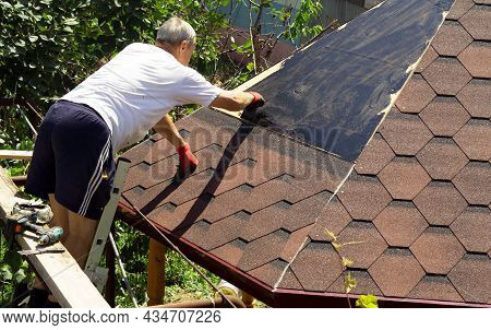 The Roofer Smears Mastic For Gluing Slate