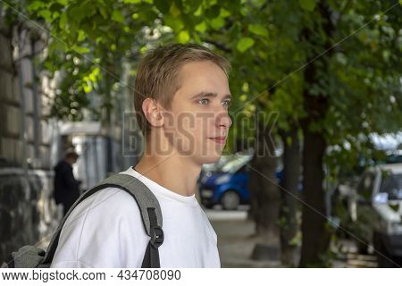 Street Portrait Of A Smiling Young Guy 20-25 Years Old With A Backpack On His Shoulder Against The B